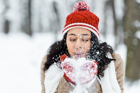 attractive african american woman blowing snow in park in winter forest