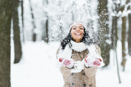 attractive african american woman throwing snow in park and smiling in winter forest