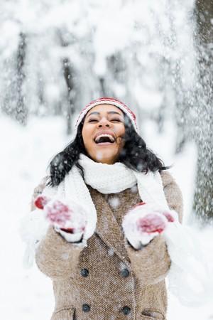 attractive african american woman throwing snow and smiling in winter forest