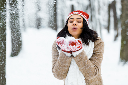beautiful african american woman blowing snow in winter forest Stock fotó