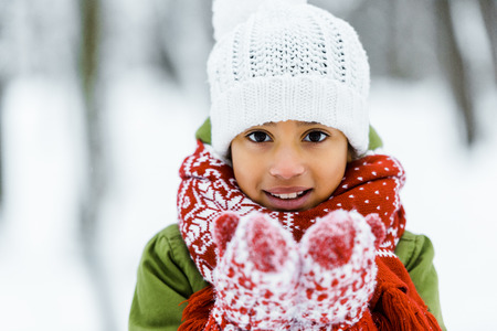 cute african american child showing white snow at camera in winter forest