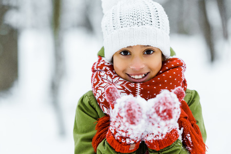 cute african american child showing white snow an smiling at camera in winter forest Stock fotó