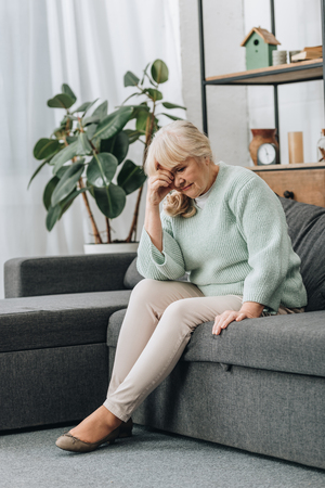 upset retired woman sitting on sofa in living room