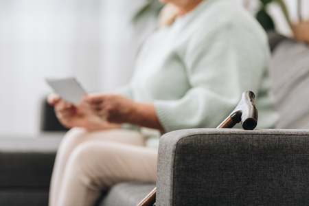 selective focus of walking stick on sofa with senior woman on background Foto de archivo - 117466130
