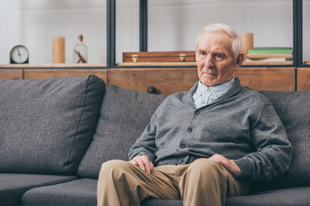 upset retired man with grey hair sitting on sofa Banque d'images
