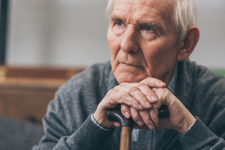 close up of retired man with grey hair holding walking cane Foto de archivo - 117466009