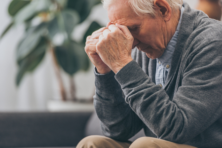 Selektiver Fokus eines verärgerten Rentners, der den Kopf hält, während er auf dem Sofa sitzt