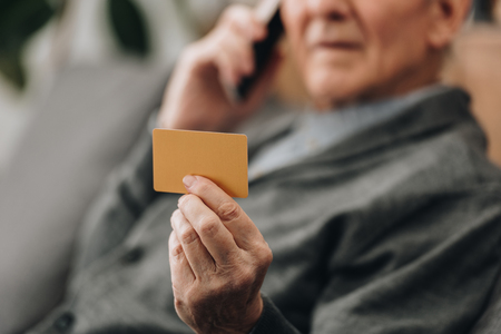 selective focus of credit card in hand of senior man