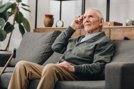 thoughtful senior man with grey hair sitting on sofa in living room Foto de archivo - 117465324