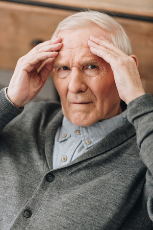 senior man with grey hair having headache