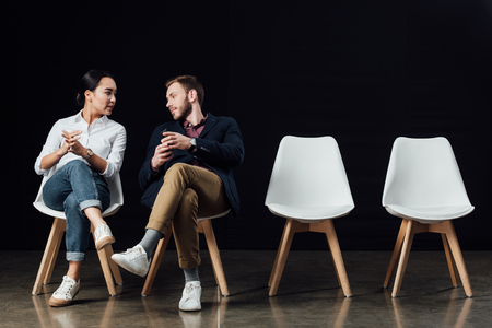 multiethnic couple sitting on chairs and talking isolated on black