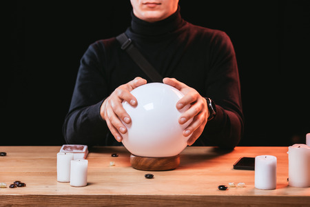 cropped view of man holding hands on crystal ball near candles isolated on black
