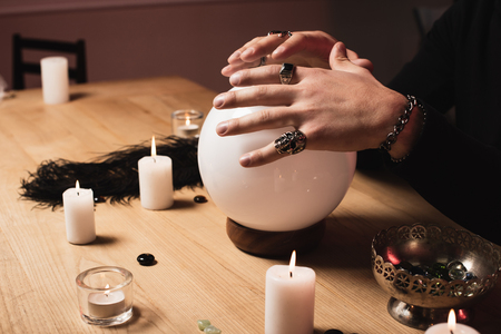 cropped view of psychic holding hands above magical crystal ball near candles Stock Photo
