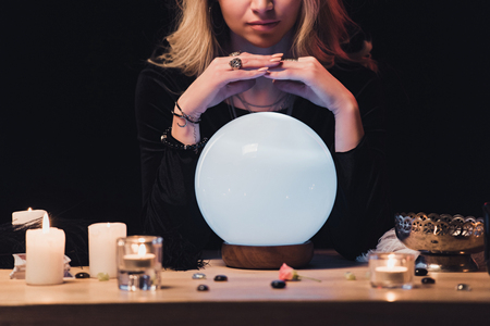 cropped view of female esoteric holding hands above fortune teller Stock Photo