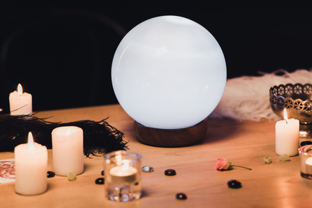 crystal ball near candles and feathers on wooden table isolated on black Reklamní fotografie