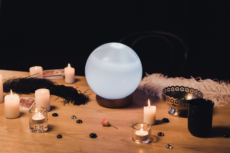 selective focus of crystal ball near candles and feathers on wooden table isolated on black Reklamní fotografie