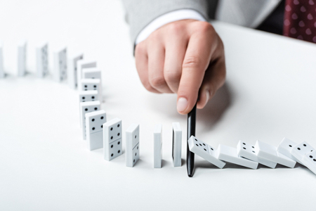 close up view of man preventing dominoes from falling with pen Stock Photo