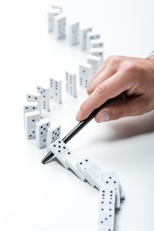 partial view of man preventing dominoes from falling with pen on white background Stock Photo