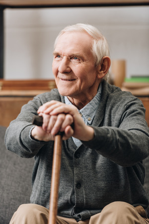 cheerful pensioner smiling and holding walking stick at home Imagens