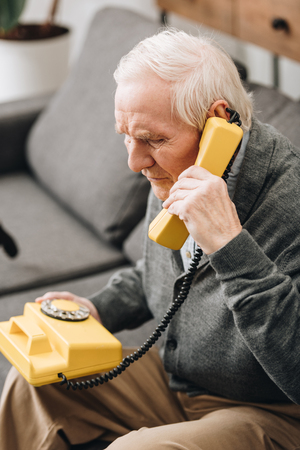 senior man talking on retro phone at home Banque d'images - 117464746