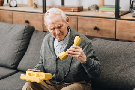 retired man looking at old phone while sitting on sofa