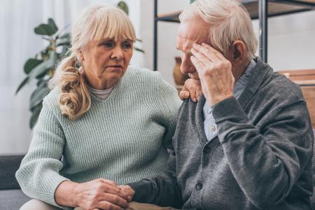 retired woman holding hands with senior husband having headache