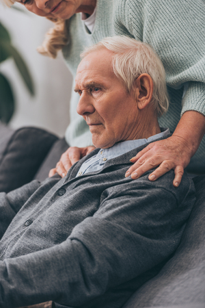 cropped view of retired wife embrace senior husband shoulders at home