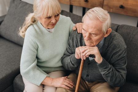 supportive senior wife sitting near sad retired husband with walking cane Stock Photo