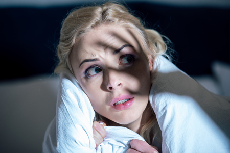 selective focus of frightened woman covered in white blanket looking away Reklamní fotografie