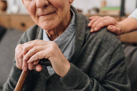 bijgesneden weergave van gelukkige gepensioneerde met vrouw handen op schouder Stockfoto