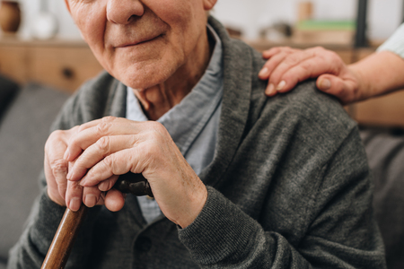 cropped view of happy pensioner with wife hands on shoulder Stockfoto