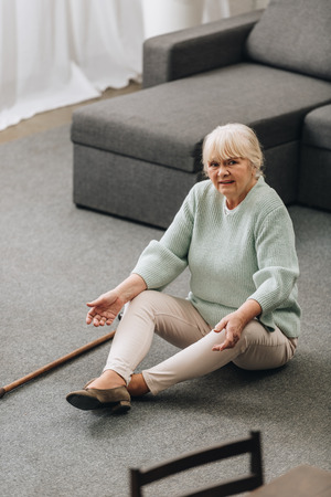 lonely senior woman with blonde hair sitting on floor with walking cane near sofa Banco de Imagens