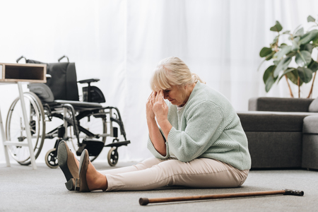 upset retired woman sitting on floor near wheelchair and holding head