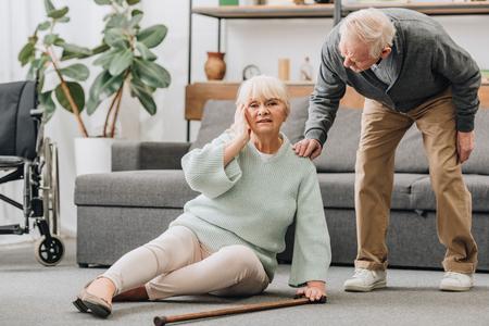 senior vrouw zittend op de vloer met hoofdpijn in de buurt van ondersteunende gepensioneerde echtgenoot