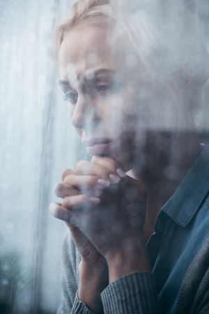 sad adult woman with folded hands at home through window with raindrops