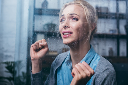 sad adult woman crying with clenched fists at home through window with raindrops Stockfoto
