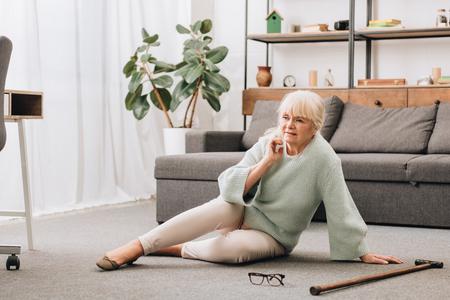 senior woman with blonde hair sitting on floor in living room Stock fotó