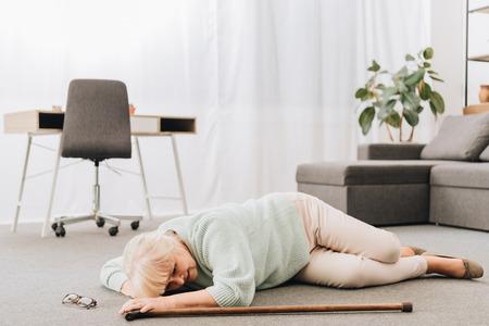 helpless retired woman lying on floor in living room