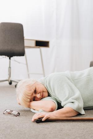 helpless senior woman lying on floor in living room