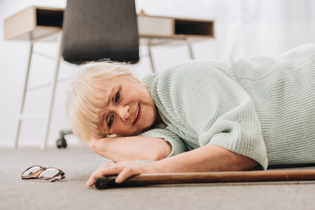 helpless retired woman with blonde hair lying on floor in living room