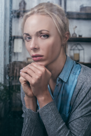 upset adult woman with folded hands looking at camera at home through window with raindrops Stockfoto