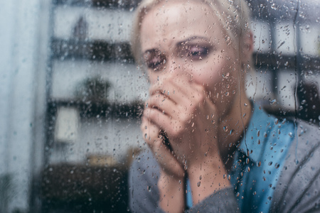 depressed adult woman with folded hands at home through window with raindrops