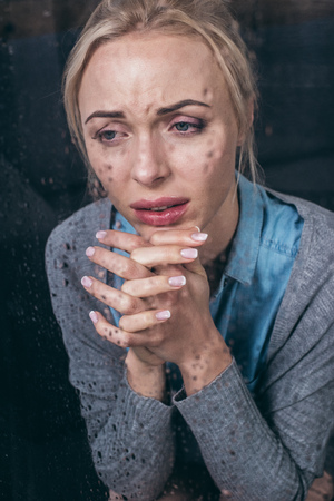 upset adult woman with folded hands crying at home through window with raindrops Stockfoto