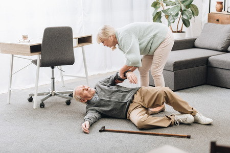 old woman helping husband who falled down with heart attack