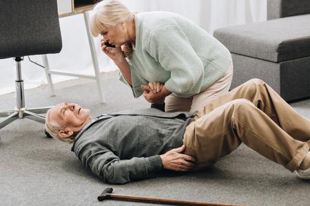 Mujer mayor mirando a su marido que cayó con un ataque al corazón y muriendo