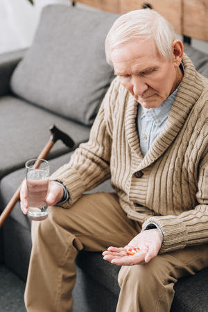 senior man holding pills and glass of water and looking at hand Foto de archivo