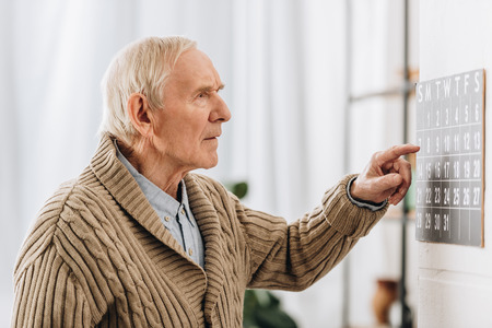 old man looking at calendar and remembering dates