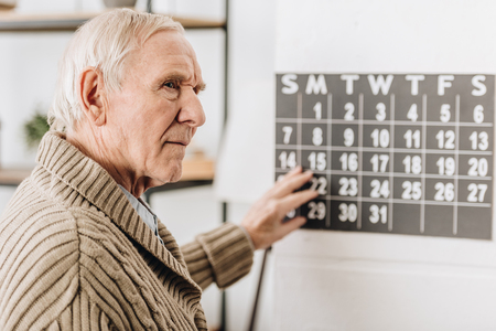 selective focus of senior man touching wall calendar and remembering dates Stockfoto
