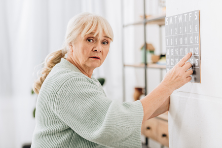 upset senior woman touching wall calendar and looking at camera Imagens - 117439769