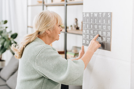 senior woman touching wall calendar and looking at dates Banque d'images - 117439770